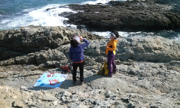 Quintessential Korean ajummas having  a picnic on hard rocks while being covered head to toe lest the sun touch any speck of their skin.